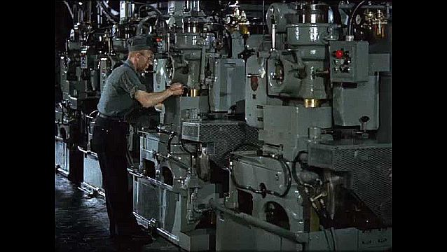 1950s: Man works in factory.  Machines produce car parts.