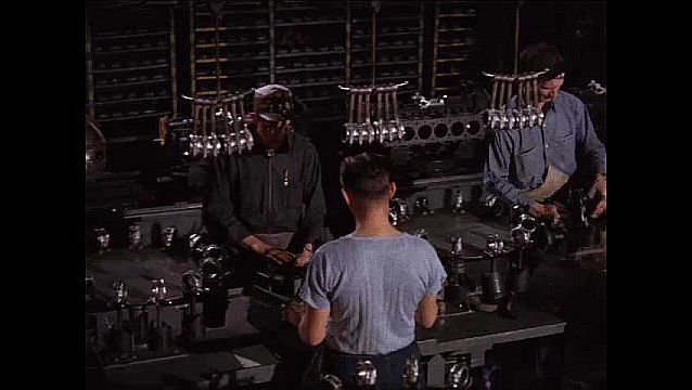 1950s: Men work on assembly line at auto plant.  Car parts emerge from machine.
