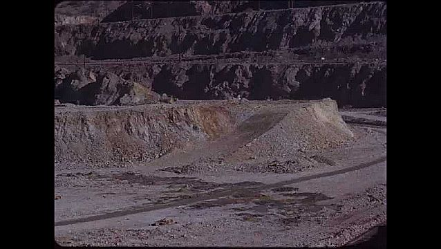 1950s: UNITED STATES: slow motion explosion in quarry. Dust settles in quarry.