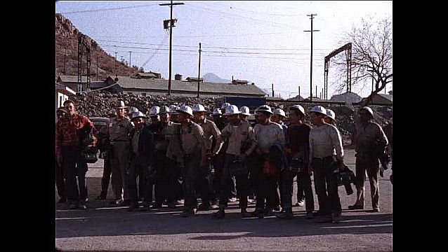 1950s: Men in hard hats walk together in group towards building.
