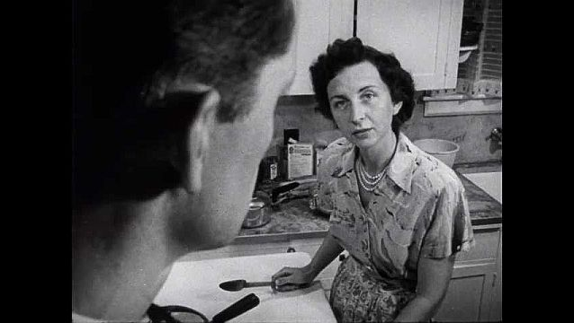 1950s: Woman in kitchen, man's face in foreground.
