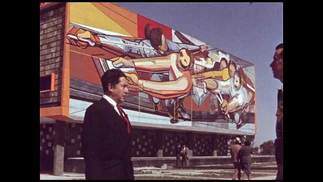 1960s: MEXICO: men admire artwork on building wall