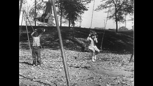 1950s: Two kids ride swings as boy pushes one of them.