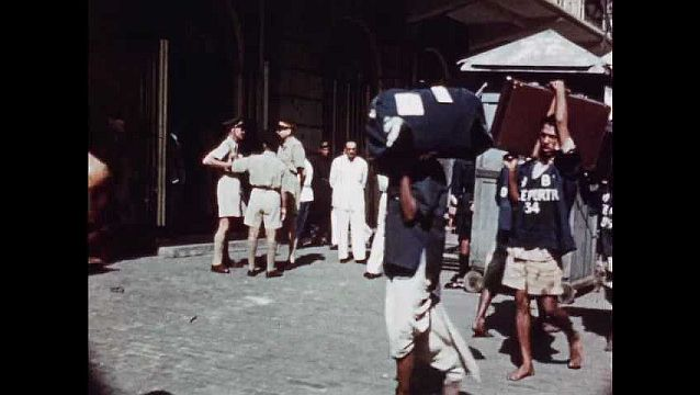1950s: Workers unload luggage. People disembark from ship. People greet each other.