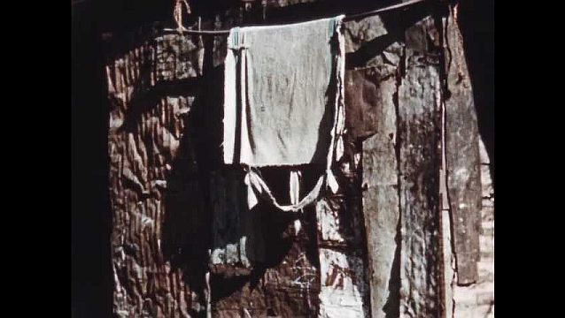 1950s: Slums.  Clothesline.  People in street.  Man lays on bed.  Men and priest talk to people.