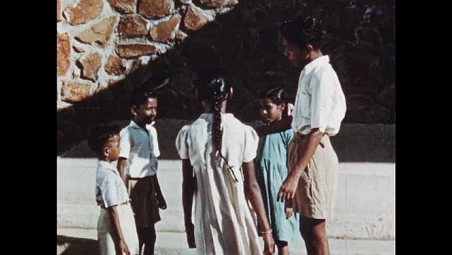 1950s: Children stand in group.  People walk into church.