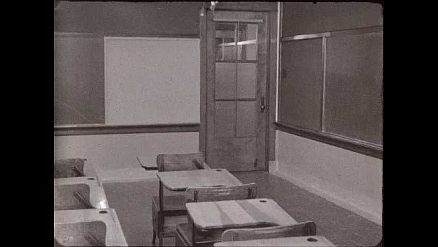1940s: Empty classroom with wooden desks and chairs. Woman in dress and high heels opens door, walks in with box and purse, puts down box on desk, pulls out plant.