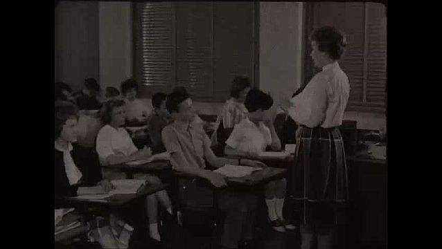 1940s: Woman stands in front of classroom, speaks, students raise hands, lower them, boy speaks, more students raise hands. Girl with high bangs speaks. Woman holds book in front of chalkboard.
