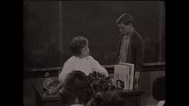 1940s: Woman stands in front of chalkboard at front of class, speaks to kids. Students looks down at their books on desks. Woman holds one of her own fingers as she speaks, students raise their hands.