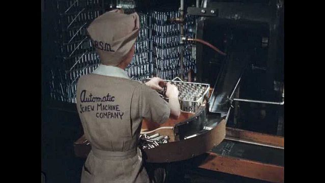 1950s: Woman places bullet shell casings as the slide down chute, into rack holder. Hands place shell casings into rack. Woman slides full rack down assembly line.