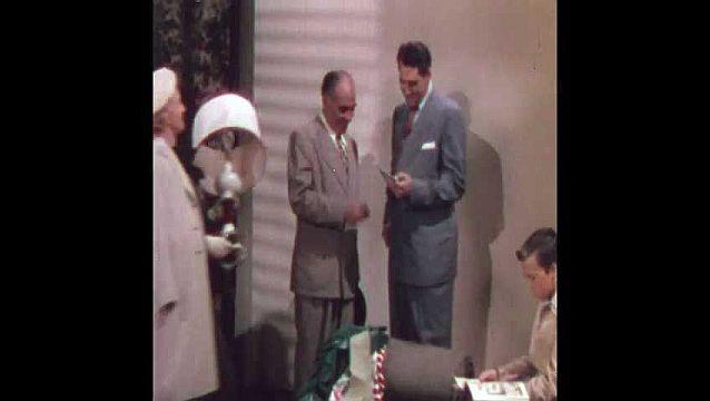 1950s: Woman holds lamp, walks up to men, talks. Men talk. Man hands money to other man. Teen girl joins group, talks. Man hands money back to other man.