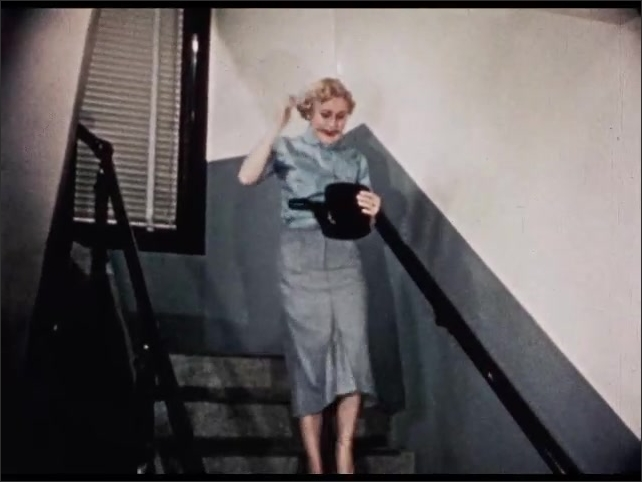 1950s: UNITED STATES: lady stands at top of stairs. Lady looks through handbag. Lady chews pencil