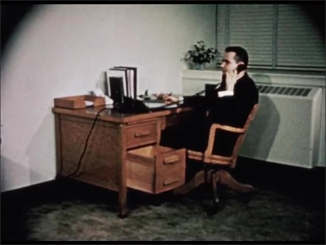 1950s: UNITED STATES: man works at desk. Man speaks on telephone. Man bangs knee on desk drawer. Lady laughs