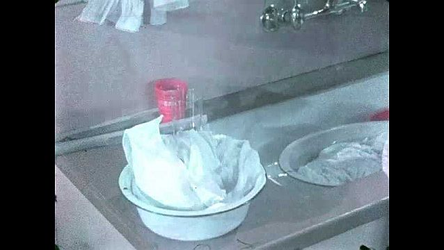 1940s: Kitchen.  Woman sprinkles powder onto folded garment in bowl.  Woman turns on water.
