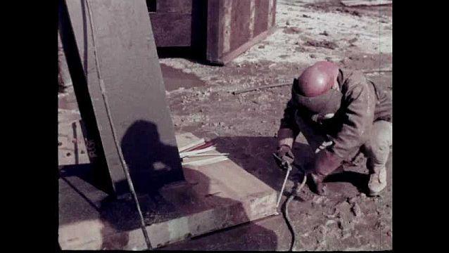 1960s: Worker welds strut. Men assist crane in placing pylon on site. Man welds steel pylon. Steel interior structure of Bell Systems pavilion. Workers construct steel infrastructure of building.