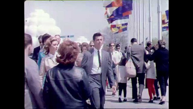 1960s: Crowds of people walk below waving flags at fairgrounds. Women talk on public telephones. Fingers push telephone buttons. Flags wave over crowds and trams at World's Fair.