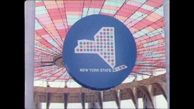 1960s: Sign for New York state. People walk across map. Elevator goes up outside of building. People walk over bridge. Buildings. Airplane hangs from ceiling.