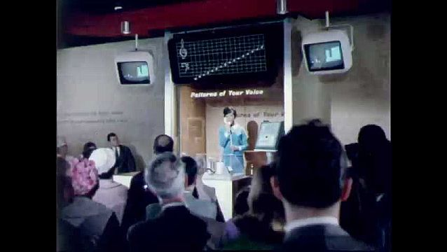 1960s: Woman stands in booth, talks, television and chat show voice pattern. People visit electronic booths at world's fair.