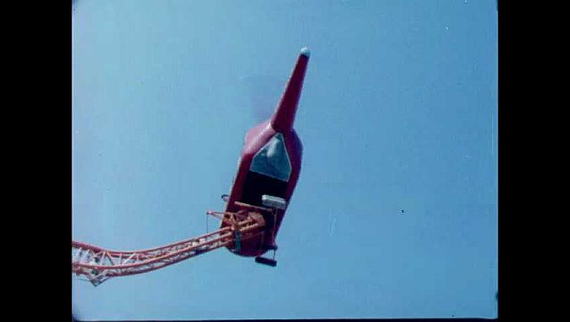 1960s: Helicopter ride. Monorail. Children ride in car. Cars travel around on track.