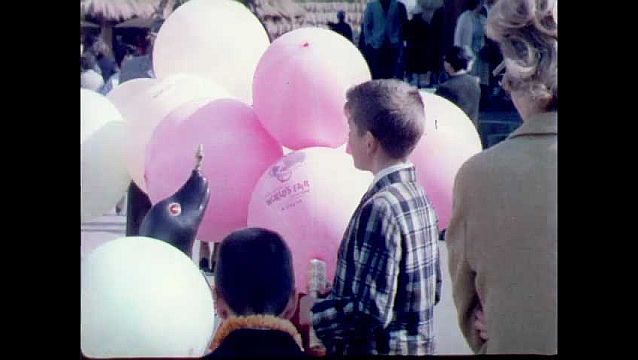 1960s: Kid plays with balloon. Child sits on man's shoulders. Flags spin around. People walk into family telephone booth.
