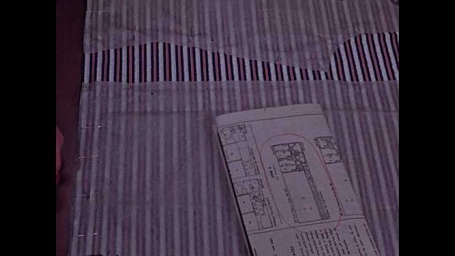 1940s: Woman's hand sweeps across fabric pinned to pattern paper, finger points to instructions, then to pins, scissors cut fabric on pattern edge. Hand holds pattern piece. Fingers point to holes.