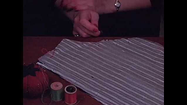 1940s: Woman's hand sews the edge of two striped fabric pieces together, two spools of thread and a tomato pincushion on the table, thimble on finger.