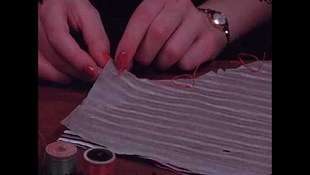1940s: Woman's hand pulls paper pattern piece off fabric to reveal red thread, scissors cut thread. Back page of instruction sheet with size measurements and a warning about shrinking.