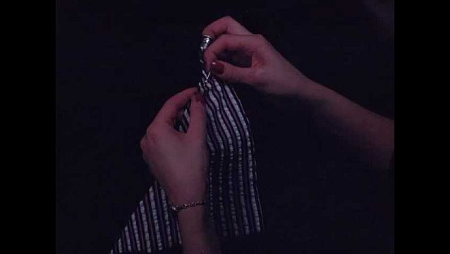 1940s: Woman's hands with red nail polish stitch the corner of striped fabric, watch on wrist, thimble on finger.
