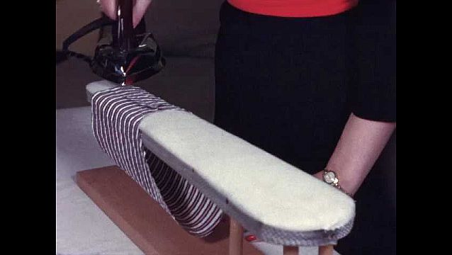 1940s: Woman's hands with red nail polish, gaudy ring and gold wristwatch, iron fabric sleeve along its seams on smaller ironing board, pulls it off, flips sleeve inside out.