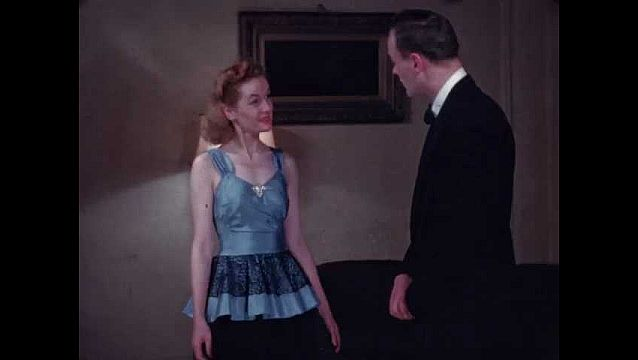 1940s: Blonde woman in blue and black gown talks to man in tuxedo, shows off her dress, spins around and smiles as man nods approvingly.