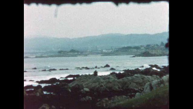 1970s: Ocean, waves, and rocks. Sailboat in ocean. People on beach.
