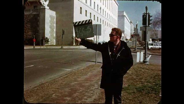 1960s: Man holds up slate for filming. Looking down street at capitol buildings. Looking at front of government building.