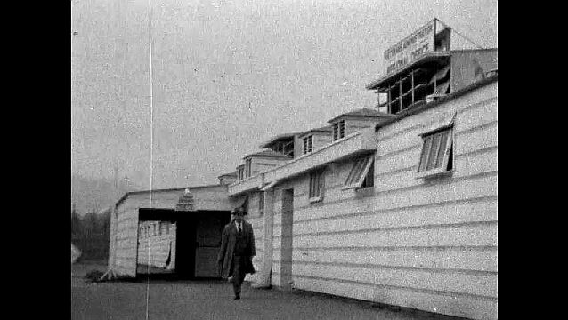 1950s: UNITED STATES: man walks past wooden building