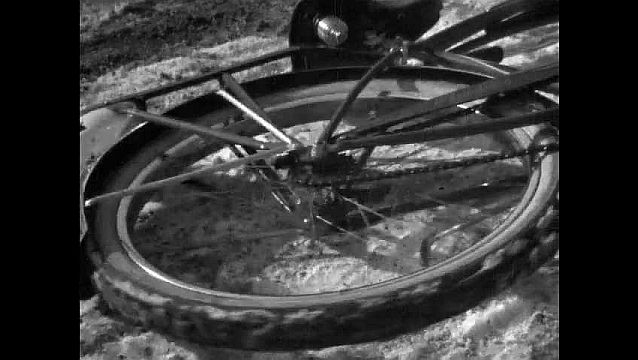 1950s: UNITED STATES: bicycle wheel spins on ground