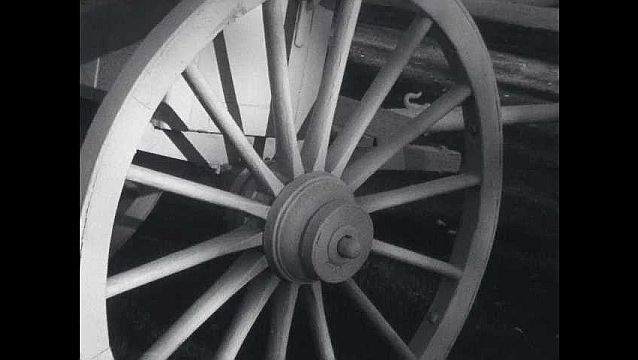 1960s: Shadow of man on large wooden wheel.