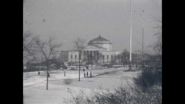 1950s: People walk through snow covered field in front of John G. Shedd Aquarium.