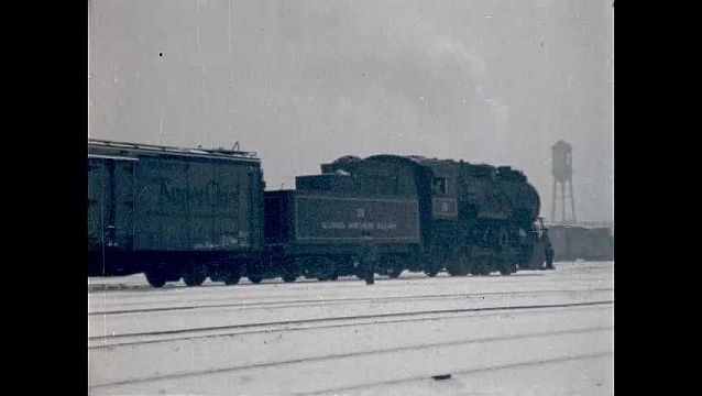 1950s: Train moves along snow covered tracks.