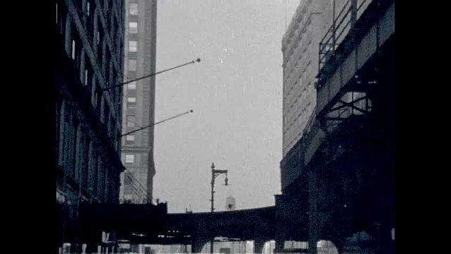 1950s: Railcar drives between buildings.