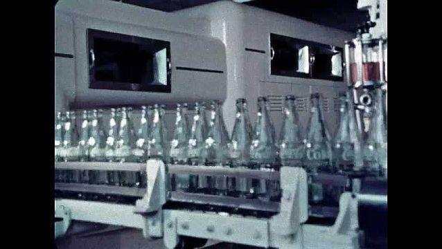 1960s: UNITED STATES: glass cola bottles in factory. Bottles on conveyor belt. Machines bottle cola