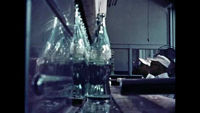 1960s: UNITED STATES: cola bottling process. Man works in factory. Cleaning of bottles