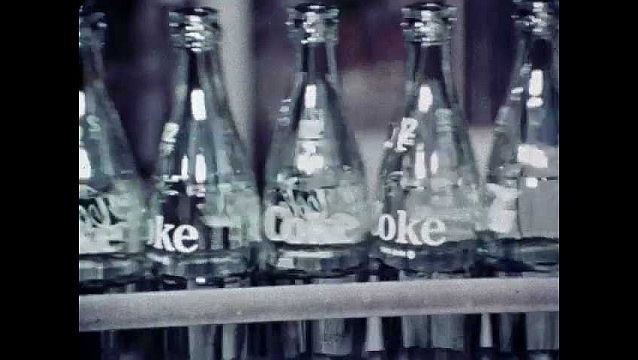 1960s: UNITED STATES: glass bottles on conveyor belt in factory. Fizz added to cola. Bottles on conveyor