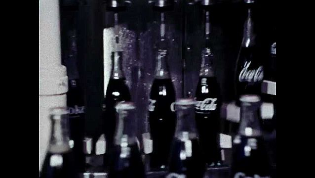 1960s: UNITED STATES: bottles on conveyor. Bottle tops, crowns, and caps. Machine and bottles.