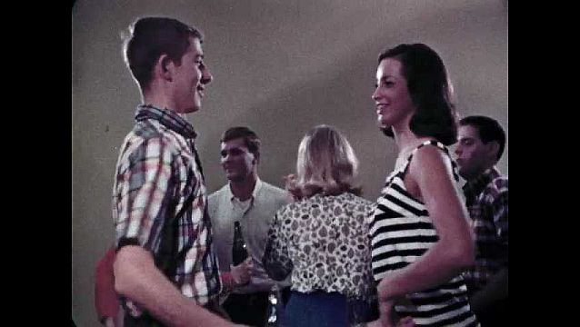 1960s: UNITED STATES: people dance at party. Bottles of cola on conveyor belt