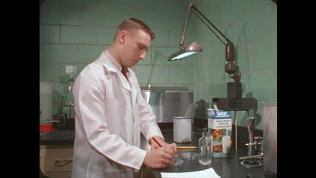 1960s: Man in lab writes notes, pulls milk from carton with glass straw, places sample milk into container.