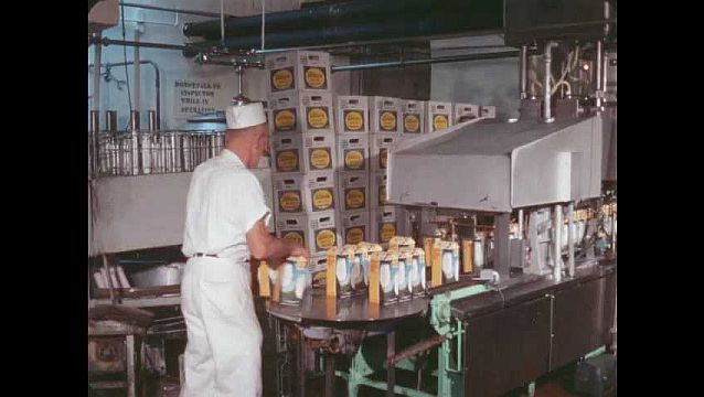 1960s: Man packages milk cartons into crates. Milk cartons move through packaging machinery.