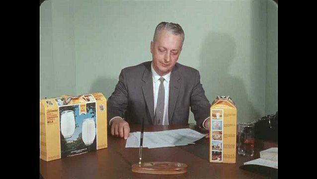 1960s: Man sits at desk, looks at papers, writes on papers.