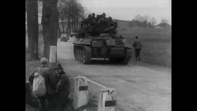 1950s: Tank driving on road. Tank passes camera. Pan of tank on road. Line of trucks on road. View through swastika on gate, cars on road.