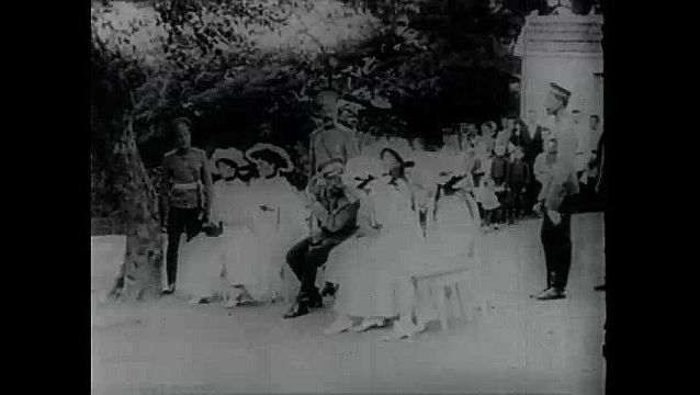 1950s: Tzar Nicholas II with family. Soldiers march in line. Soldiers walk down steps with guns. Soldiers walk over bodies. Soldiers fire guns. People running. People run down steps. Cannons fire.
