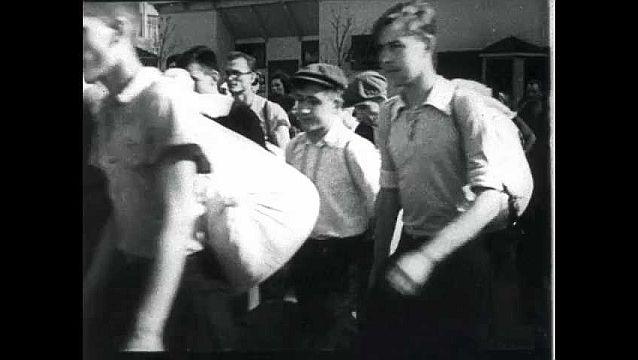 1950s: Men walking. Soldier talking, turns. Close ups of men. Men marching. Man loads gun. Tanks firing. Tanks driving up hill.