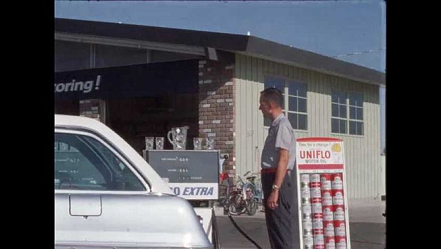 1960s: Gas station attendant stands next to trunk of silver sedan and a display of Uniflo Motor Oil, he pulls the hose from the pump, pumps gas into the sedan.
